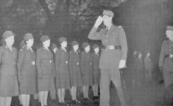 Le général de Gaulle passe en revue cette unité de volontaires, dont la tenue ne le cède en rien à celle de leurs collègues hommes (RFL).