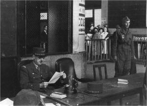 Le général de Gaulle installé à la gare Montparnasse, sur le quai de départ des voies. Il prend connaissance de l'acte de capitulation que vient de signer le général von Choltitz. À droite, ci-dessus : le capitaine Christian Girard, aide de camp du général Leclerc (coll. Pérez).