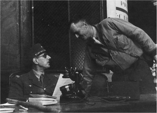 Le général de Gaulle installé à la gare Montparnasse, sur le quai de départ des voies. Il prend connaissance de l'acte de capitulation que vient de signer le général von Choltitz. Le général Leclerc fournit au général de Gaulle des explications sur les conditions de la reddition allemande (coll. Pérez).